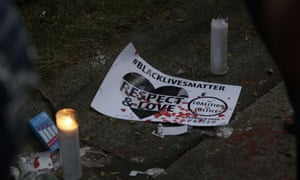 A sign and candle are seen at the location where Sylville Smith was shot and killed by Milwaukee police .