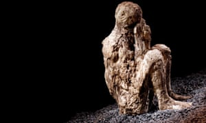 A resin cast of a crouching man covering his mouth with a hooded cloak he was wearing before he was overcome by the eruption of Mount Vesuvius.