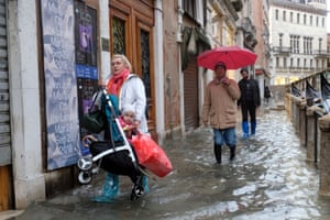 People walk in the flooded St Mark's Square during a period of seasonal high water