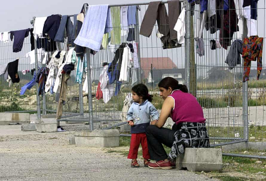 Asylum seekers wait for their clothing to dry at the fence of the Sangatte refugee camp in northern France.