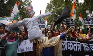 Congress party workers carry an effigy of Narendra Modi protest outside the BJP office.