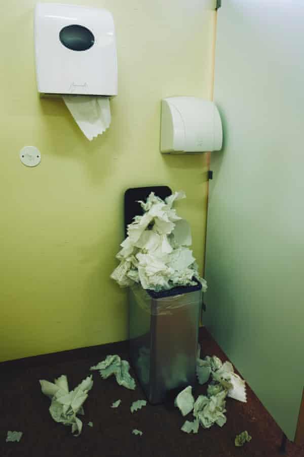 A restroom paper towel dispenser, hand dryer and an over full bin