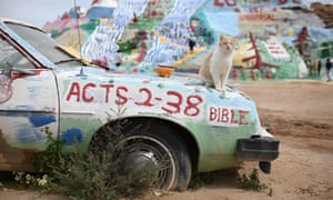A cat sits on a painted car at Salvation Mountain, a hillside covered with Biblical messages and symbols built over a thirty-year period by outsider artist and Vermont native Leonard Knight, in Slab City, California, US