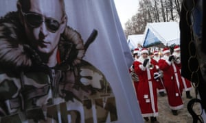 A santa band walk past a kiosk selling Putin t-shirts in St.Petersburg