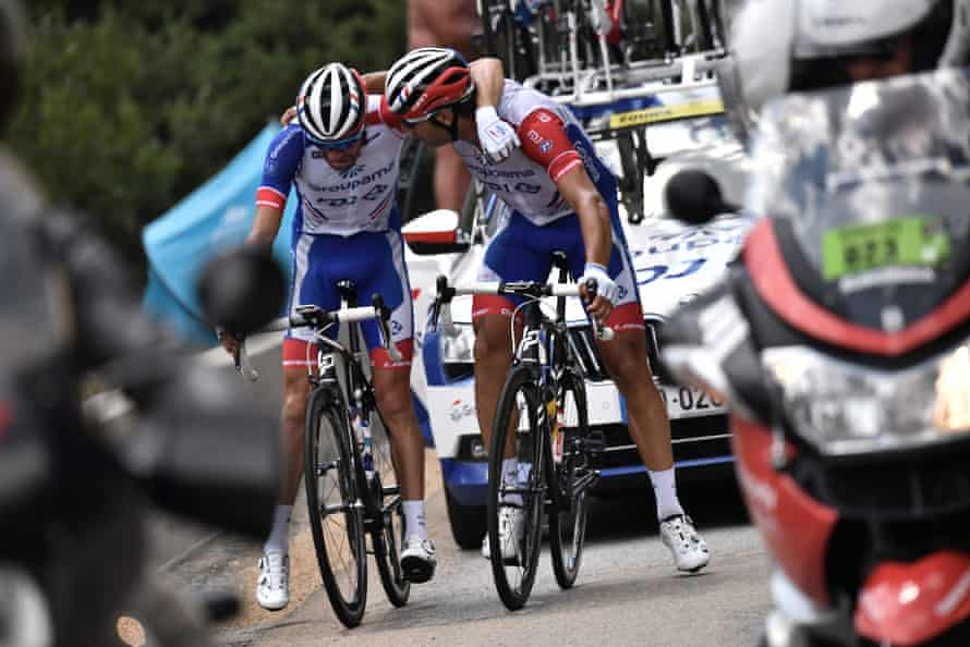 Thibaut Pinot (left) is comforted by a teammate as he stops on Stage 19 and is forced to quit the race due to pain in his left leg