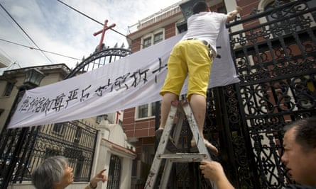 """Church members put up a banner reading """"safeguard the dignity of belief"""" in China's eastern Zhejiang Province in 2015."""