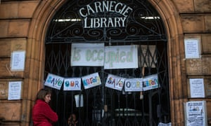 A protester stands outside Carnegie library in South London during its occupation in protest against cuts