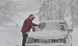 A driver clears snow from his vehicle in Casaglia, Mugello on Tuesday.