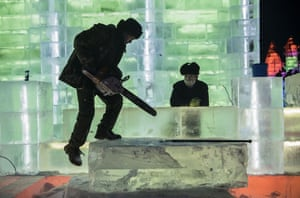 A laborer prepares to cut into a large ice block