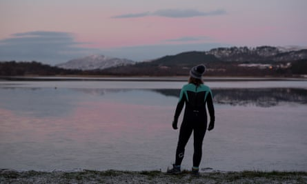 Man in a wetsuit and wolly hat by the side of a loch in Scotland at first light.