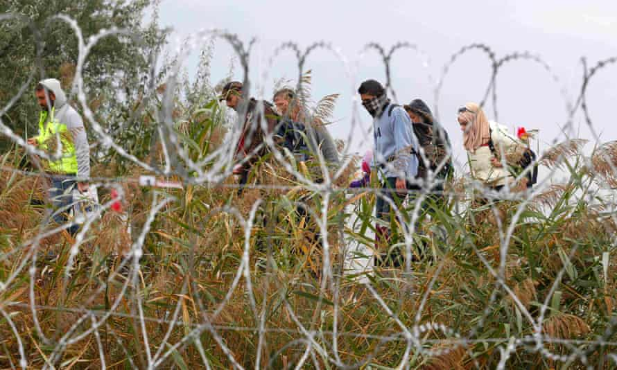 Refugees pass a barbed wire fence in Röszke, Hungary.