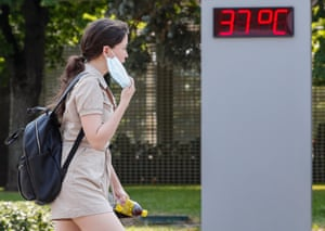 A woman removes her face mask as temperatures reach a sweltering 37C (98.6F)