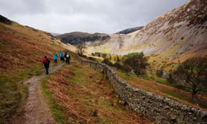 Walkers on the path above Glenriddding Beck heading for Red Tarn in the Lake District national park.