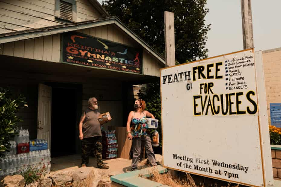people exit building with supplies. sign says 'free for evacuees'