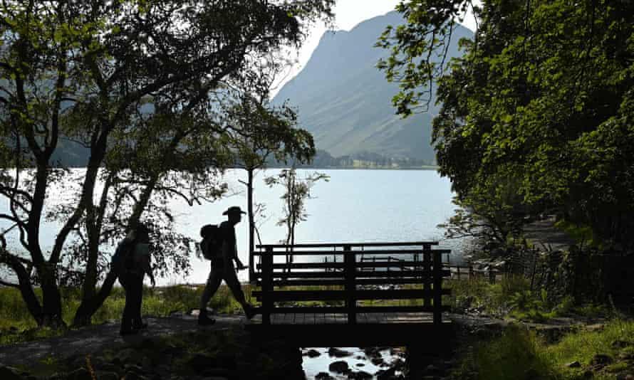 Walkers cross a footbridge beside Buttermere Lake.