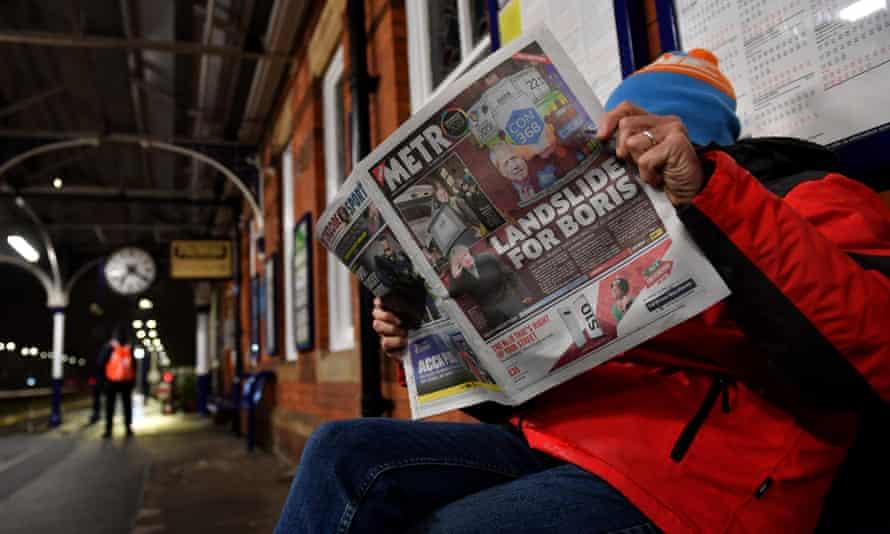 Man reading the Metro on a station platform