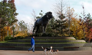 A man walks his dogs in CS Lewis Square, which commemorates the Chronicles of Narnia author