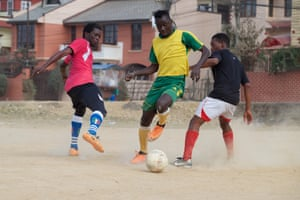 John Junior from Burkina Faso takes on defenders at a football ground on the southern outskirts of Kathmandu