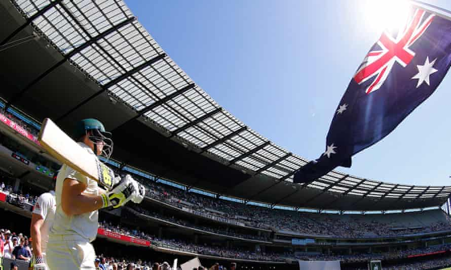cricketers wielding bats are seen walking out before crowded stands at the MCG