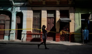 A woman walks past houses in quarantine amid concerns about the spread of the coronavirus disease  in Havana