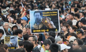 "Protesters in Hong Kong, one carrying a sign reading ""Extradite to China, disappear forever""."