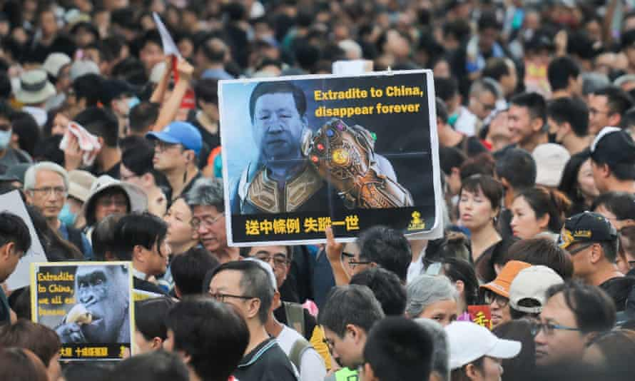 """Protesters in Hong Kong, one carrying a sign reading """"Extradite to China, disappear forever""""."""