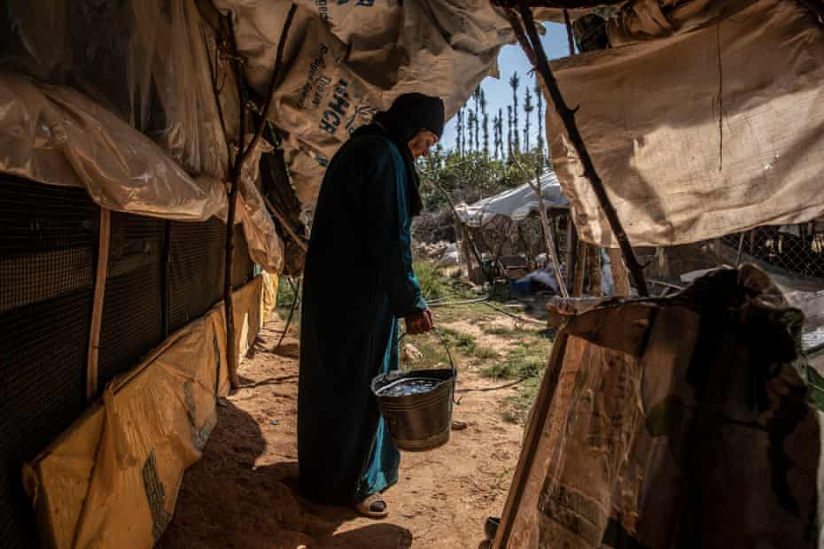 Foza, 75, transporting water next to her tent