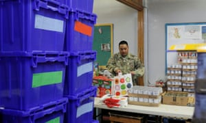 A New York national guard member distributes supplies to New Rochelle, which has been hit hard by the coronavirus.