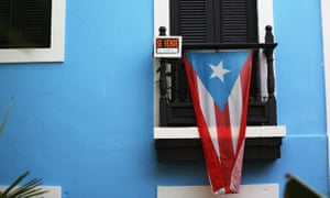 A for sale sign is seen hanging from a balcony next to a Puerto Rican flag in Old San Juan