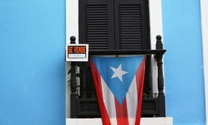 A for sale sign hangs next to a Puerto Rican flag on a balcony in San Juan.