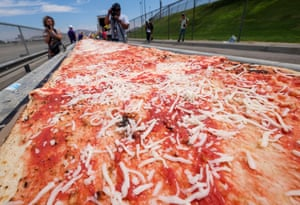 Fontana, CaliforniaVolunteers work on an attempt to make a 2.13 km pizza to break the world record for longest pizza. The current record is 1,853.88 m and was achieved by Napoli Pizza Village