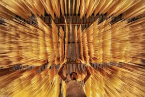 A worker inspects whether rice noodles are dried correctly.