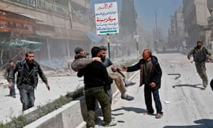 Syrians carry an injured man following a reported government air strike on the rebel-controlled town of Hamouria