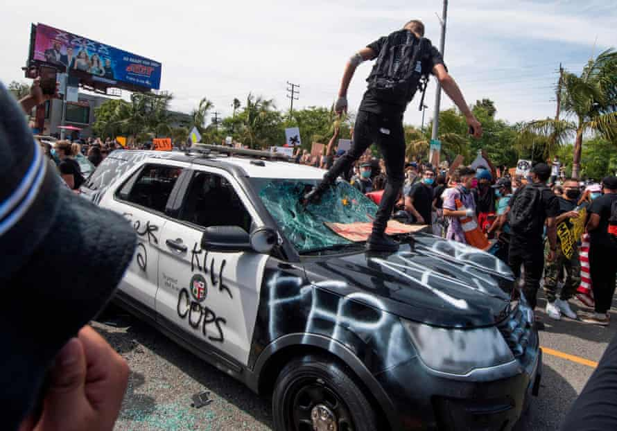 Demonstrators smash a police vehicle in the Fairfax District, in Los Angeles, California