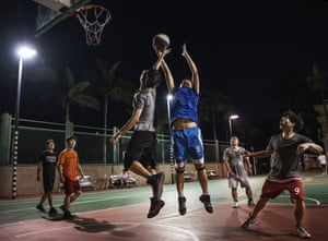 Employees play basketball at a recreation area in staff housing at the end of the work day at the Bantian campus
