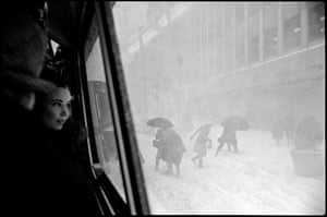 USA. New York City. 1967. Girl in bus and figures in street during snowstorm.