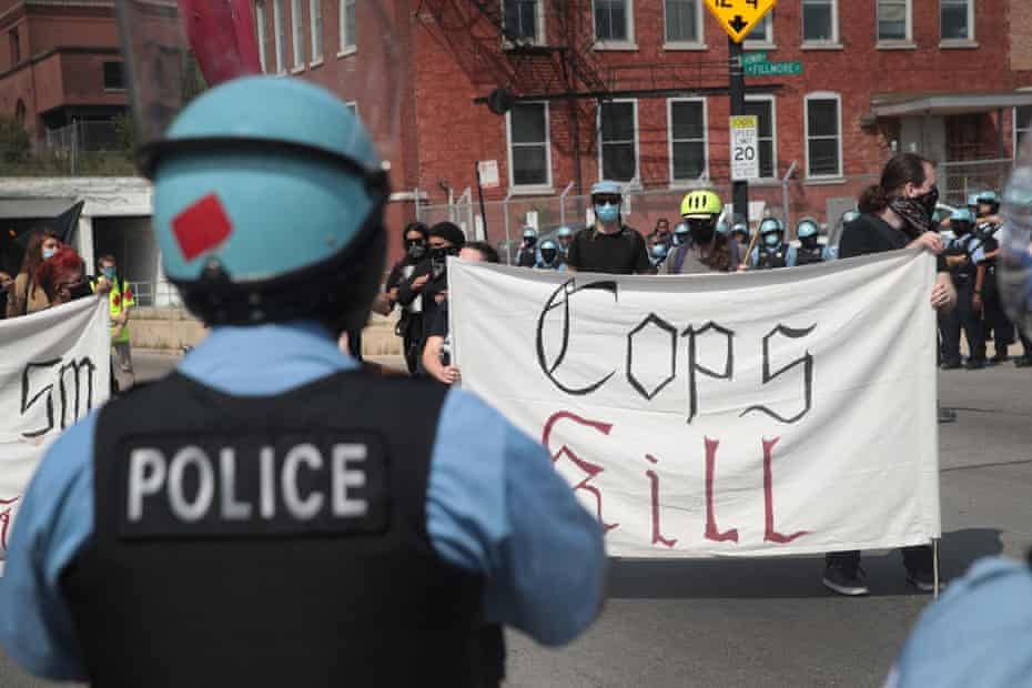 Police stand guard as pro and anti-police demonstrators gather outside of the Homan Square police station in Chicago on 15 August.