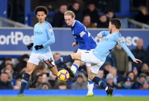 Tom Davies of Everton passes the ball despite the challenge of David Silva of Manchester City.