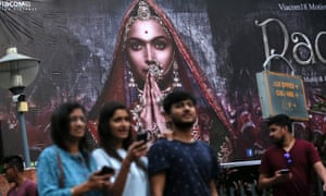 People walk past a poster for the Bollywood movie Padmavati in Mumbai