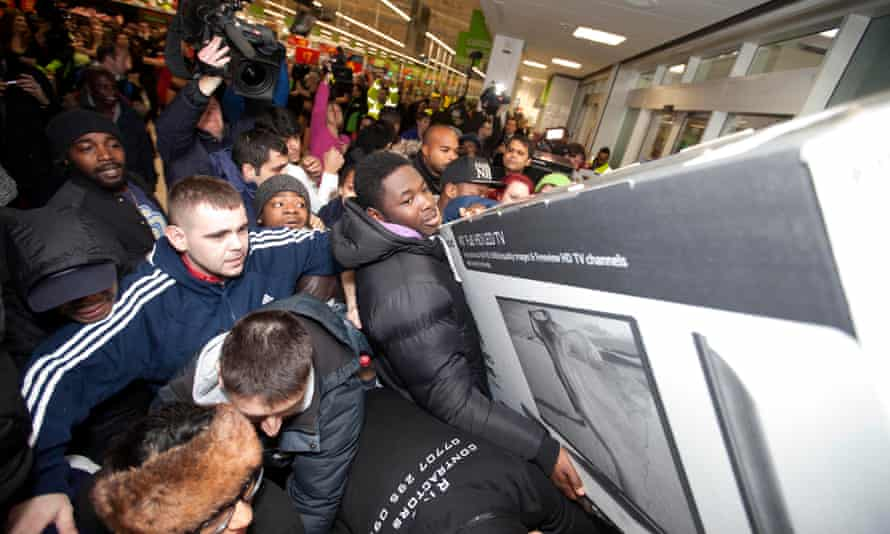 A crowd of people fight over a giant TV