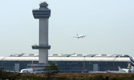 An aircraft flies past the control tower as it prepares to land at New York's John F Kennedy Airport.