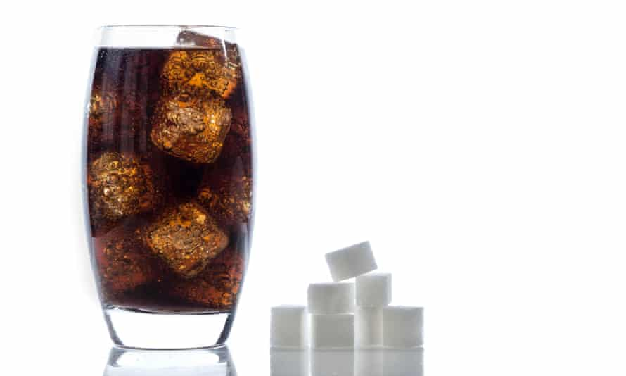 A glass of cola and some sugar cubes
