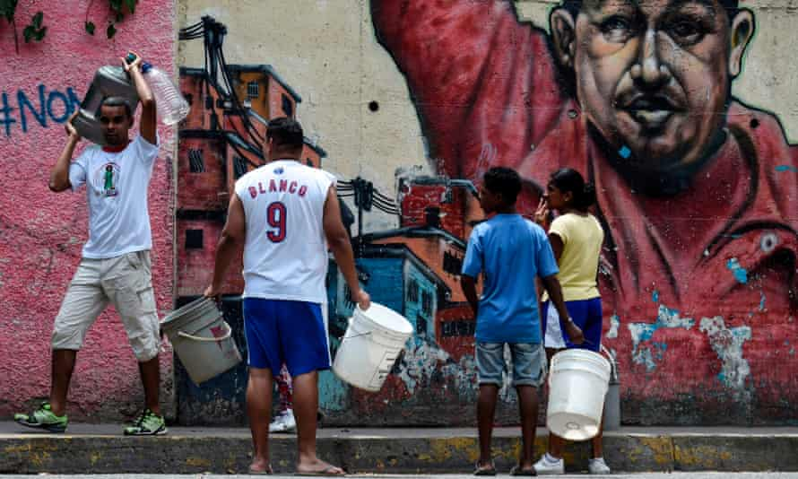 Venezuelans head to collect water from a sewage canal at the river Guaire in Caracas. Maduro has alleged the US conducted the attack on the country's electrical system.
