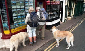 Couple with dogs looking in estate agent's window