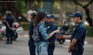 Kendall Jenner handing a bottle of Pepsi to a man in police uniform
