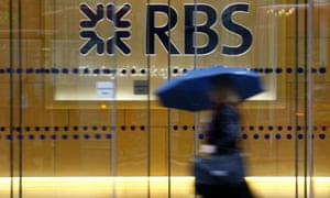 A woman with an umbrella passes the RBS HQ in London