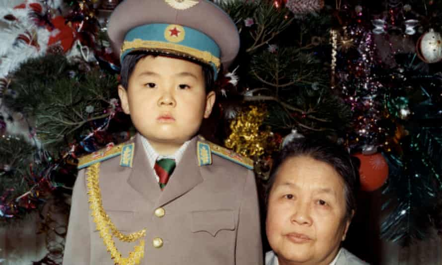 Kim Jong-nam as a young child dressed in an army uniform poses with his maternal grandmother.