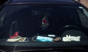 Face masks and gloves on the dashboard of a vehicle during the coronavirus disease outbreak