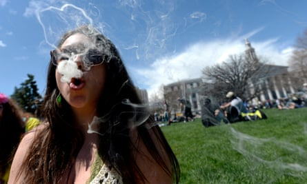 A woman blows smoke rings with marijuana smoke during the 4/20 Rally at the Civic Center in Denver, Colorado, in 2014.