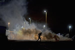 Migrants flee as police fire teargas into the entrance of the camp known as the 'New Jungle' in Calais, France